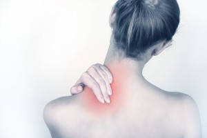 Woman holds a hand on pain neck ** Note: Slight blurriness, best at smaller sizes